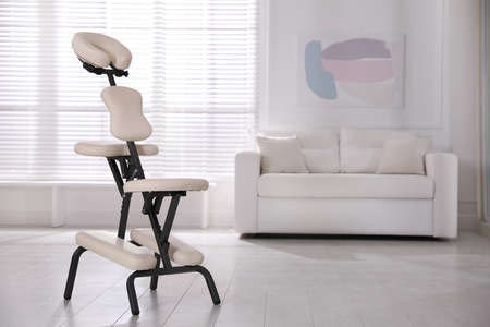 Modern massage chair in office, space for text. Medical equipment