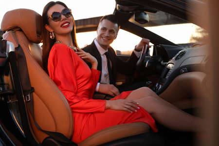 Beautiful couple in luxury convertible car outdoors