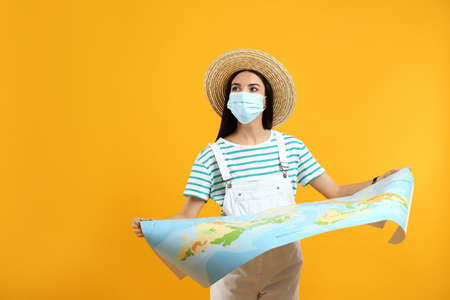 Female tourist in medical mask with map on yellow background, space for text. Traveling during pandemic Фото со стока