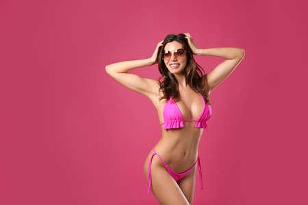 Beautiful woman in stylish bikini and sunglasses on crimson background Фото со стока