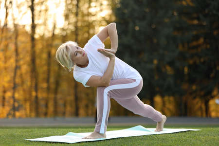 Mature woman practicing yoga on green grass in park