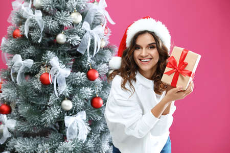 Happy young woman in Santa hat with gift near Christmas tree on pink background Фото со стока