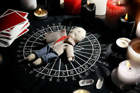 Voodoo doll pierced with needle surrounded by ceremonial items on table