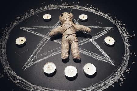 Voodoo doll pierced with pins and candles in pentagram on black table Zdjęcie Seryjne