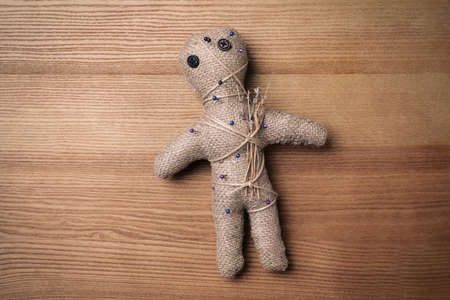 Voodoo doll pierced with pins on wooden table, top view