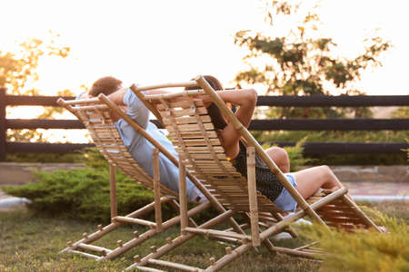 Couple resting in deck chairs outdoors. Summer vacation