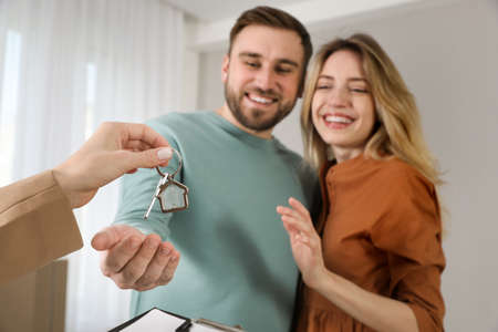 Real estate agent giving key to happy young couple in new house, focus on hands