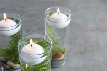 Candles, stones and fern leaves in glass holders with liquid on gray table, closeup Foto de archivo