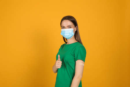 Vaccinated woman with protective mask and medical plaster on her arm showing thumb up against yellow background