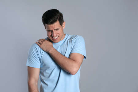 Man suffering from shoulder pain on gray background. Space for text