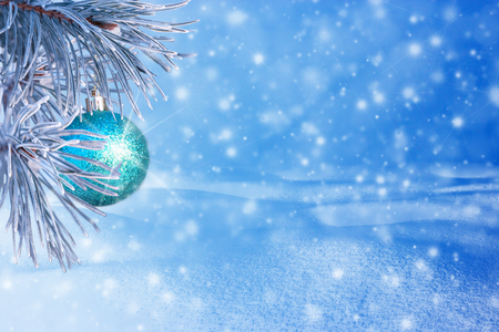 Winter landscape with snow. Christmas background with fir branch and Christmas ball.Merry Christmas and happy New Year greeting card with copy-space. Stock Photo