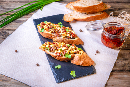 Bruschetta with feta cheese, dried tomatoes, olive oil and fresh microgreen herbs, on a stone plate on a wooden table. Delicious Mediterranean vegetarian appetizer.