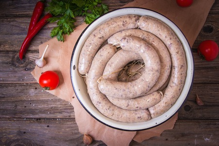 Raw fresh white sausages on a plate with vegetables. Weisswurst in a heap. Traditional Bavarian or Munich white sausage made from sliced veal and pork bacon. Oktoberfest concept.