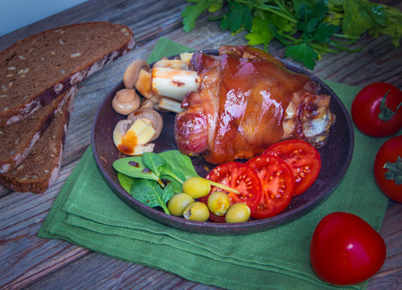 Delicious grilled pork knuckle with fresh spinach leaves, sliced red tomatoes and marinated champignons. Tasty food. Stock Photo