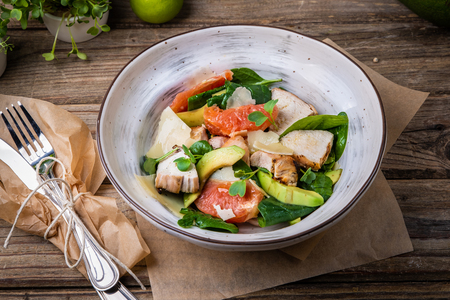 Fresh dietary salad of baked chicken breast, avocado, grapefruit slices, spinach leaves, cheese, olive oil and microgreen. Healthy food. Detox.
