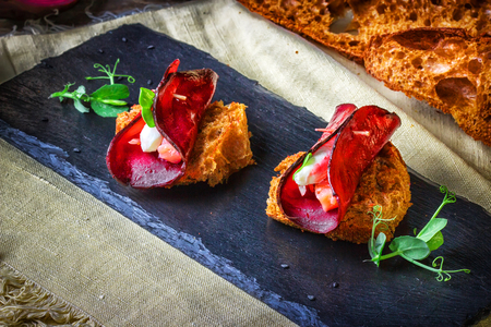 Toasts with a circle of beets, goat cheese and a piece of salmon on a black slate on a background of rustic napkin.Decorated with shoots of green peas leaves.