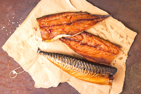 Smoked mackerel fillets on craft paper on a rustic rusty metal table. Top view. Reklamní fotografie