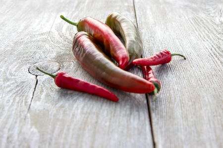 Various fresh hot red chilli pepper on wooden background.