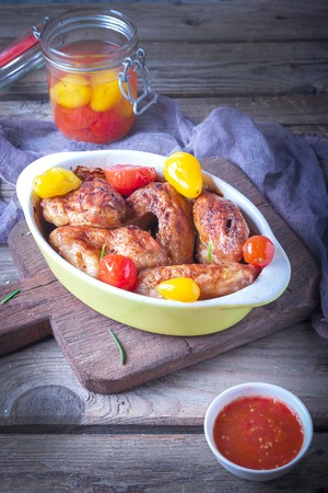 Chicken Wings, Oven Baked and Grilled. Homemade Tasty Food. Pickled colorful tomatoes.Wood Table Background, Rustic Still Life Style.
