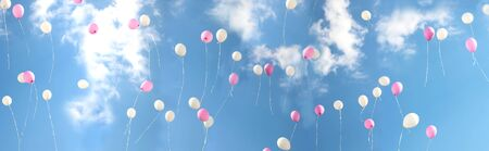 Beautiful, colorful, white-pink  bouncing balls fly against the background of a blue sunny sky and white fluffy clouds. Long format. Banner.