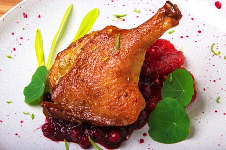 baked duck leg on red grapefruit with cranberry sauce