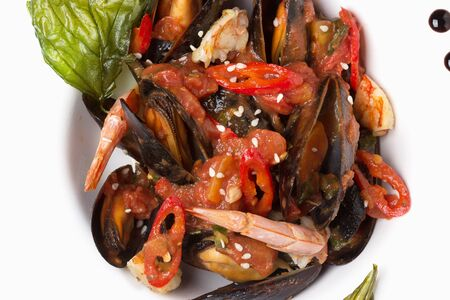 Mussels in a sauce of sweet pepper and tomato, with shrimp and sprinkled with sesame seeds