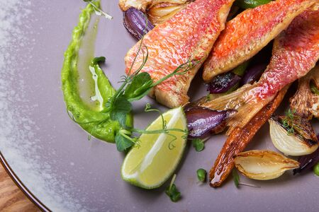 Sea bass with grilled vegetables, carrots, garlic, cauliflower, asparagus and decorated peas microgreens