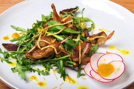 Fried quails on arugula salad with fried potato chips on a white plate on a wooden background 版權商用圖片