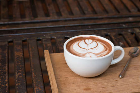 metalic: Coffee in a cup on a wooden tray