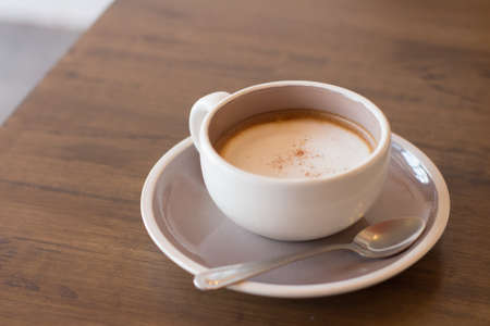 Coffee in a cup on a wooden table with a spoon