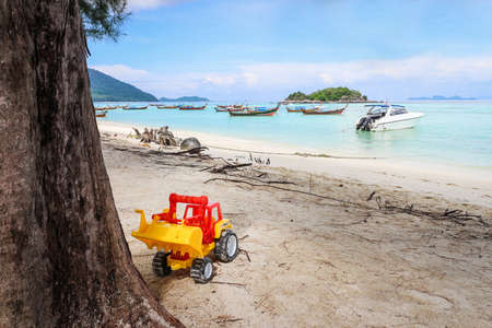 Toy car under the tree on Lipe island with boat parking in the background