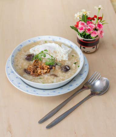 Rice porridge with garlic and egg breakfast in white bowl on wooden table