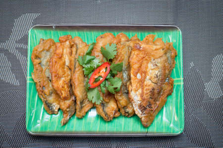 Fried mackerel on a plate with condiments Stock Photo