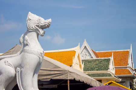 White marble leo guarding the entrance of the temple in Thailand