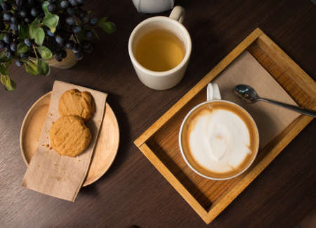 Cookies, tea, and coffee on a dark wooden table
