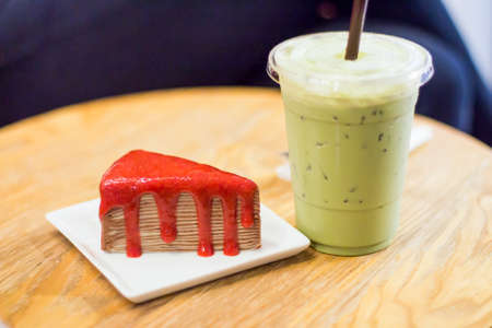 Crape cake with iced green tea on a wooden table