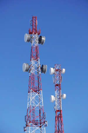 amplification: towers of mobile operators on a background of blue sky Stock Photo