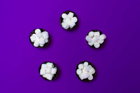marshmallows in the forms for cakes on a purple background, five pieces. Arranged in a circle. View from above. bright colours.
