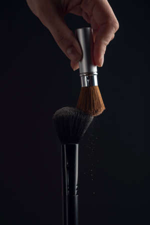 two powderbrush opposite each other on black background.