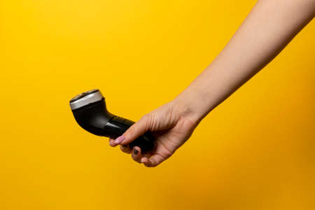 male electric razor in a female hand on a yellow background. Minimalism