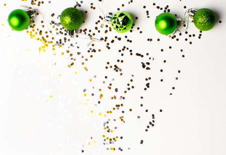 Christmas toys of green color and silver and gold confetti on a white background. Flat lay, top view, copy space. Christmas composition. Stockfoto