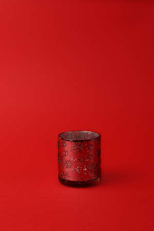 glass candlestick with ornament of snowflakes on a red background. Vertical photo. Copy space. Christmas concept. Minimalism. Zdjęcie Seryjne