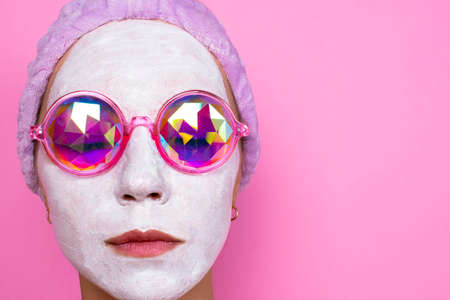 girl in cosmetic white mask and pink glasses smiles on a pink background. Spa concept