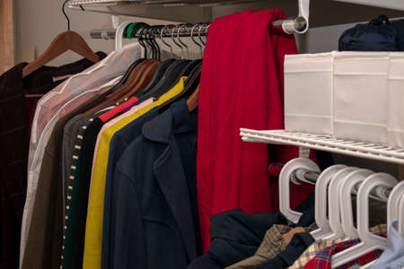 Rail with multi-colored clothes on hangers and in containers. Open storage system. horizontal photo.