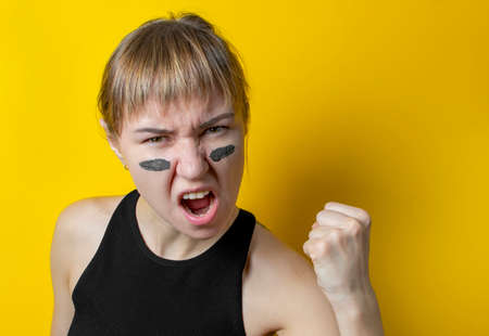 a woman with camouflage on her face on a yellow background shows a fist and shouts a battle cry. feminism concept Stock Photo