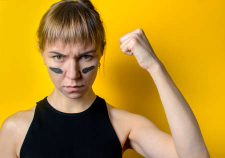 a woman with camouflage on her face on a yellow background shows a fist. feminism concept Stock Photo