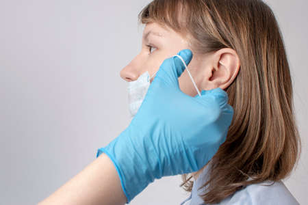 mans hands puts a protective mask on woman mouth.
