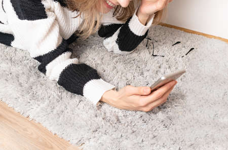 smiled girl lies on a fluffy carpet and looks at the phone. Standard-Bild