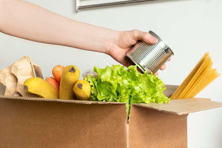 Box with food for delivery on a white background. A female hand in a medical glove puts can in a box with products. Concept of donation, food delivery
