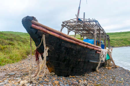 Old abandoned wooden fishing boat in blue color on the beach. A fishing net hangs from the sides.